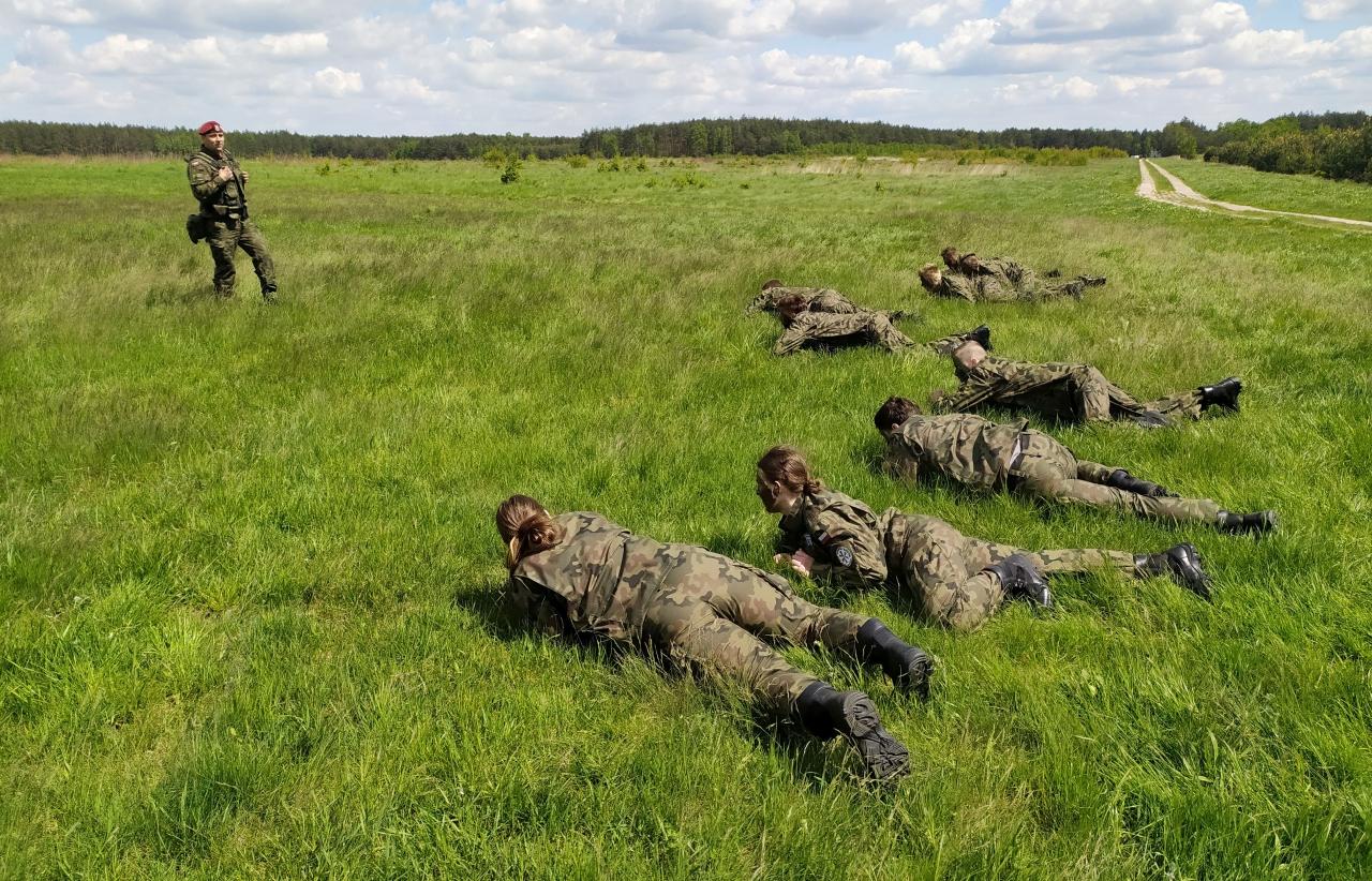 Grupa młodzieży czołga się po trawie wczasie ćwiczeń fizycznych