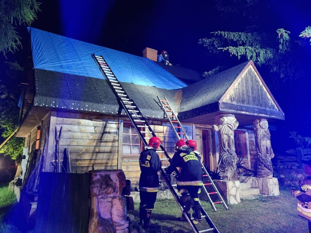 Trzech strażaków zabezpieczają dach budynku mieszkalnego, który został zniszczony przez nawałnicę