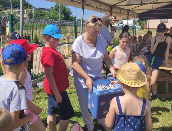 Grupa dzieci częstuje się lodami wczasie organizowanego pikniku rodzinnego wMzurkach