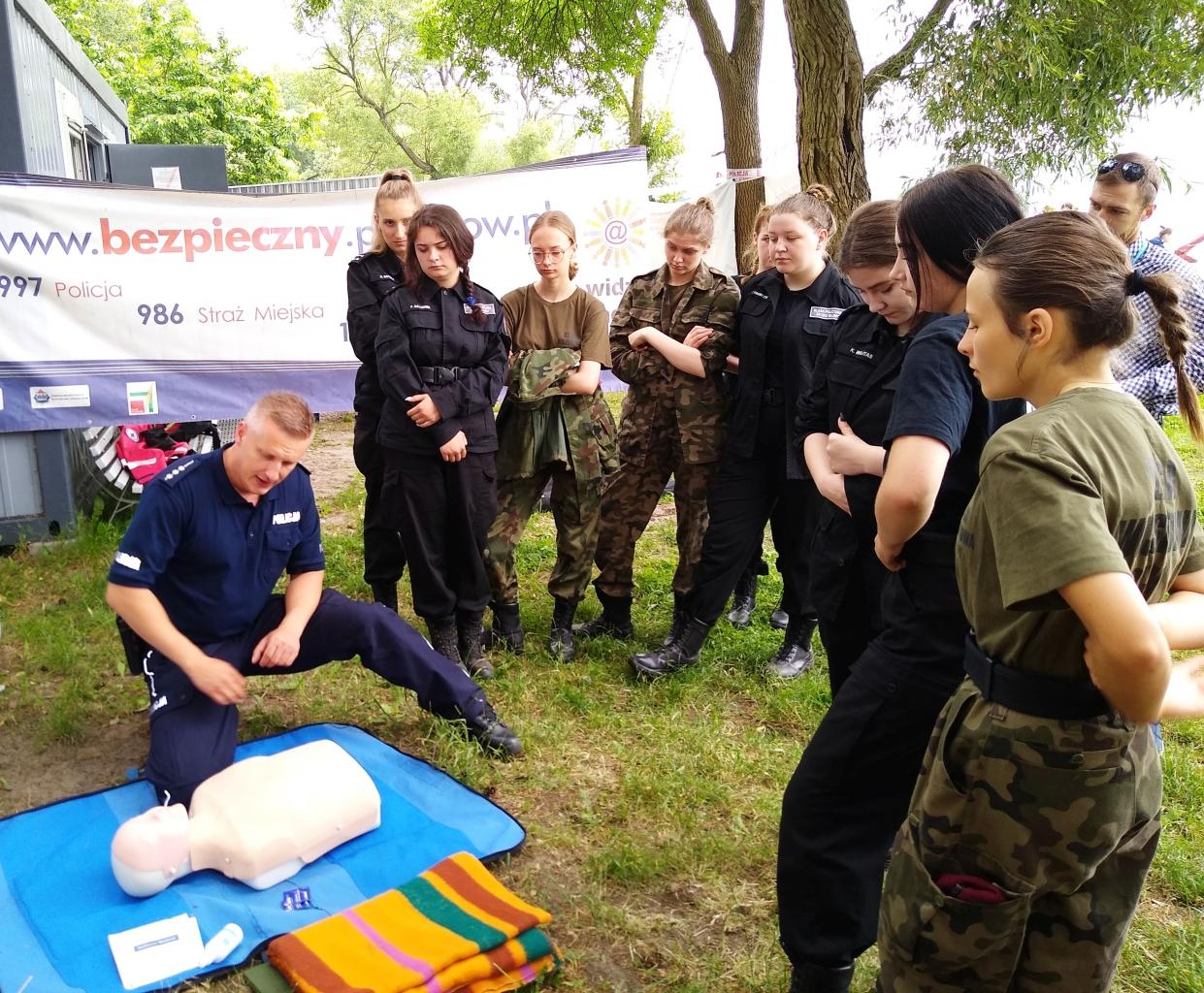 Młodzież obserwuje potencjalną akcję ratowniczą wykonywaną przez policjanta