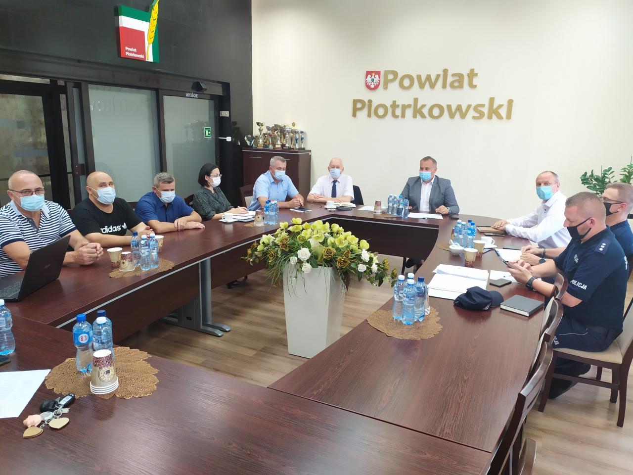 Zaproszeni na posiedzenie sztabu kryzysowego goście siedzą przy stole wsali Zarządu Powiatu Starostwa Powiatowego wPiotrkowie Trybunalskim