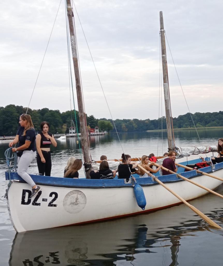 Grupa ludzi na jachcie znajdującym się na wodzie.