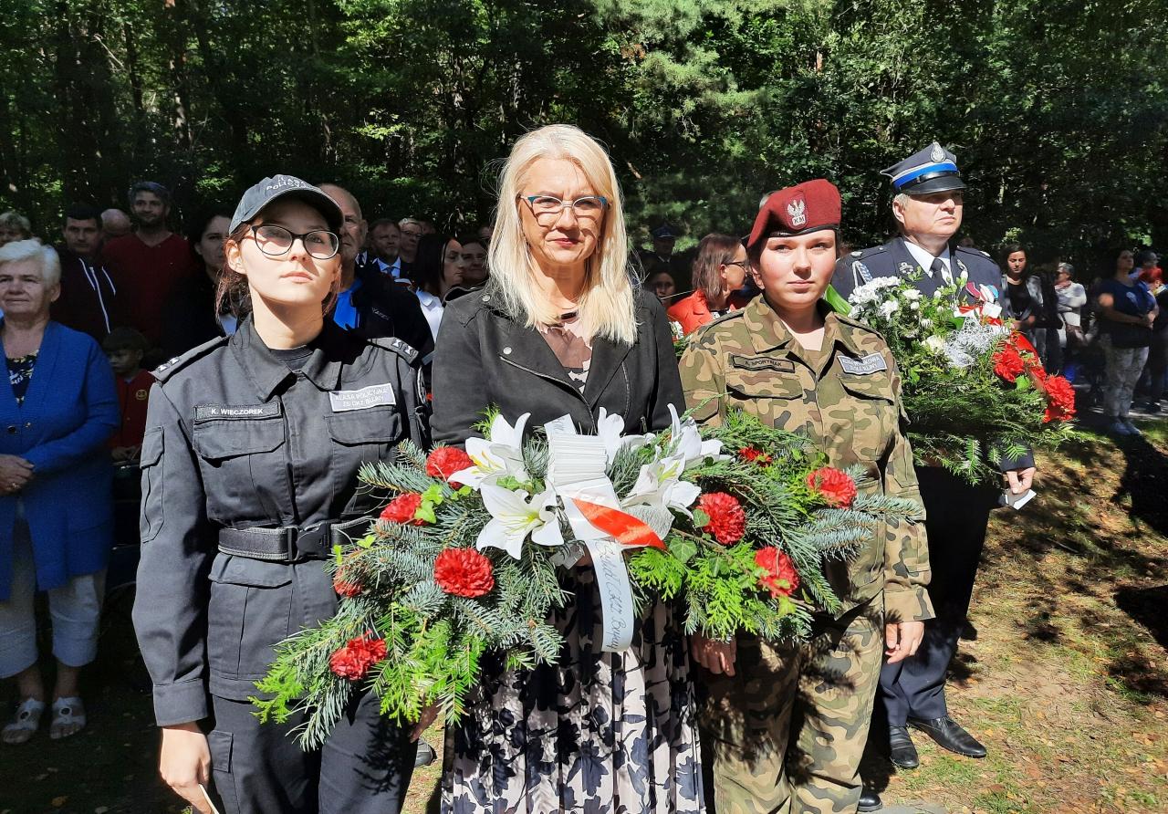 Dyrektor szkoły wraz zuczniami składa wiązanekę kwiatów pod pomnikiem poległych wobronie Gór Borowskich