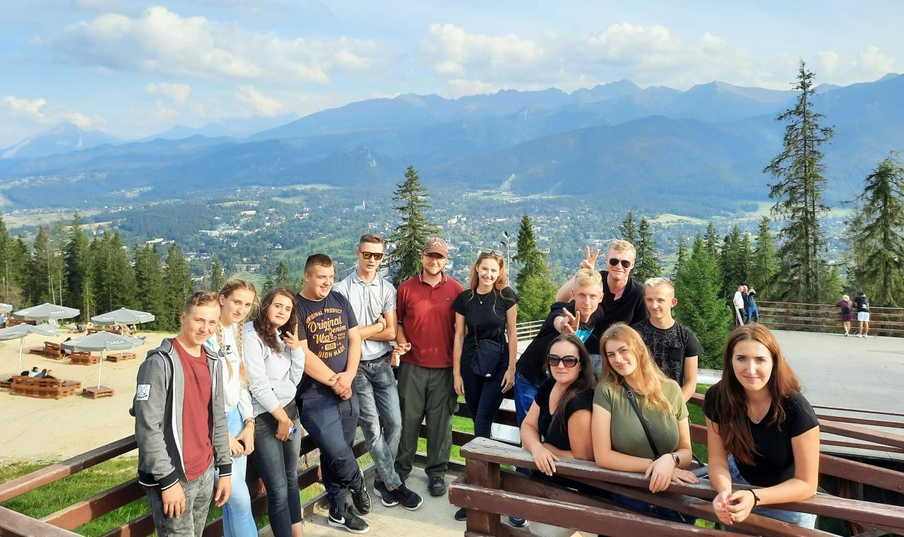 Grupa klikunastu uczniów stoi na tle gór.