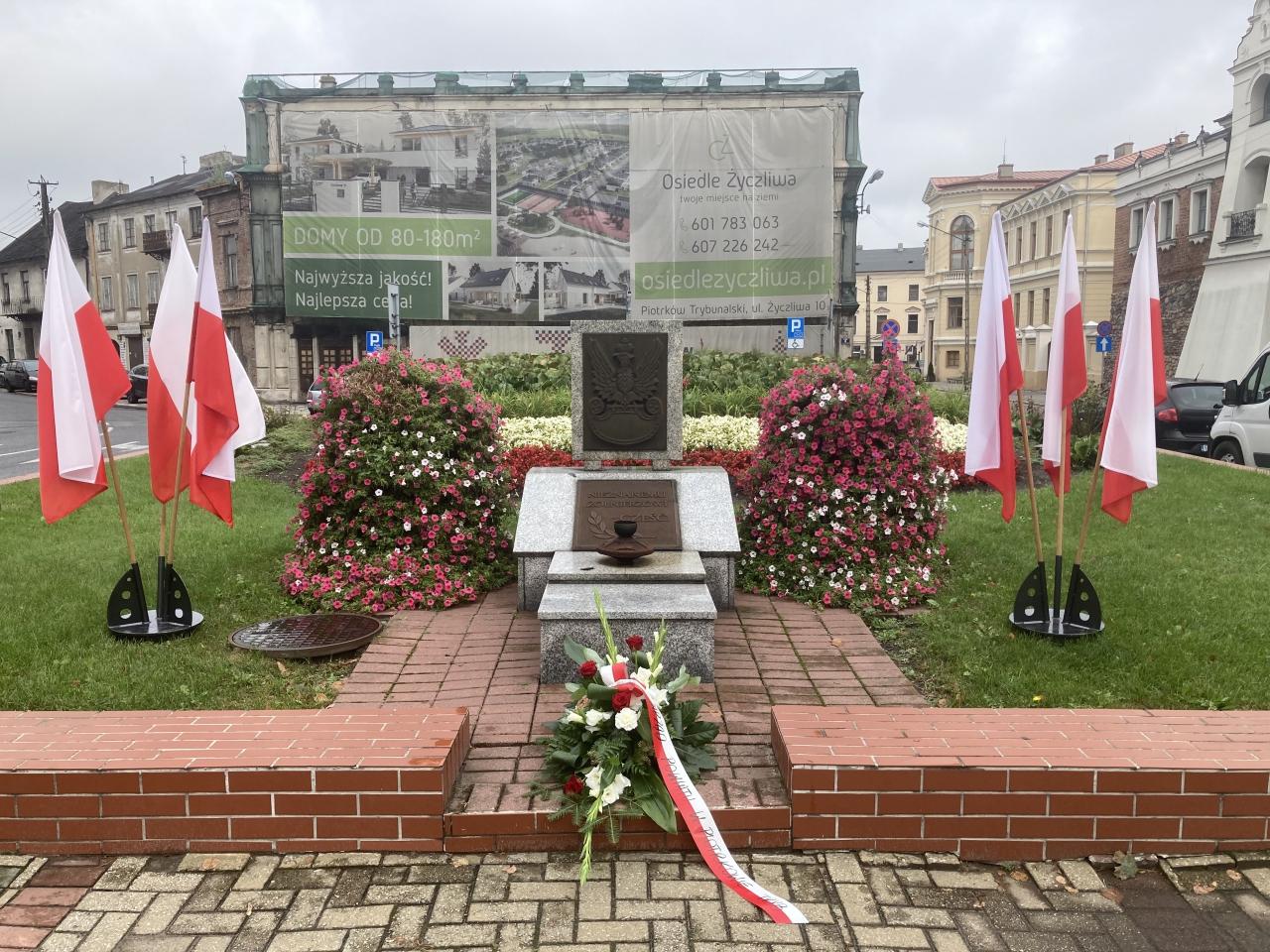 Pomnik, wokół flagi ikwiaty.